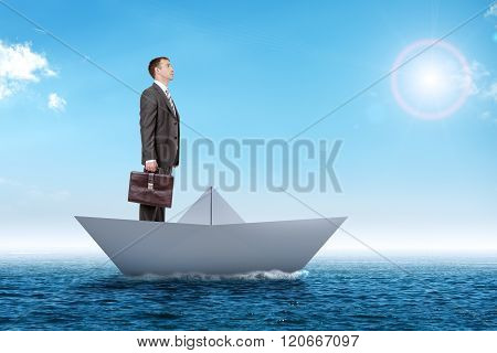 Businessman in paper boat