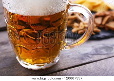 Mug of beer and snacks on wooden table