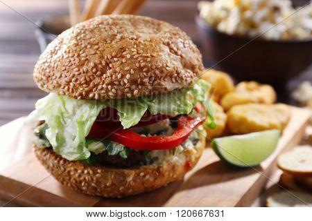 Big tasty hamburger with snacks on wooden table