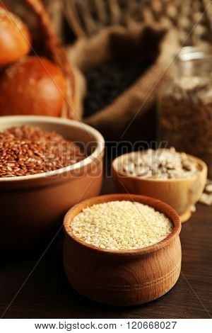 Composition of sesame, flax, sunflower seeds and buns on wooden table background, closeup