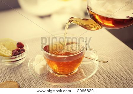Tea cup and kettle on the table beside sofa