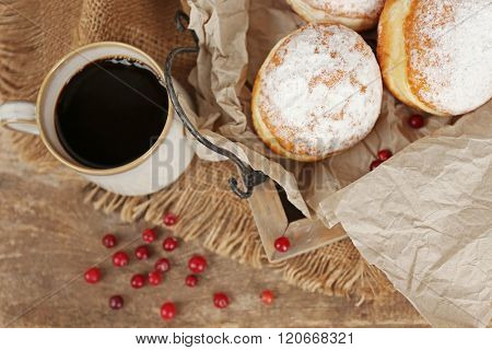 Delicious sugary donuts with red currant on wooden tray with parchment closeup