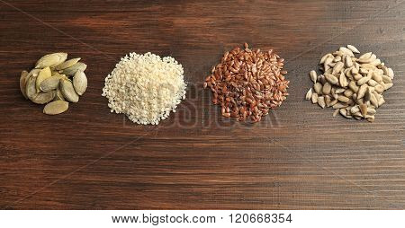 Heaps of sesame, flax, pumpkin and sunflower seeds on wooden table background, closeup
