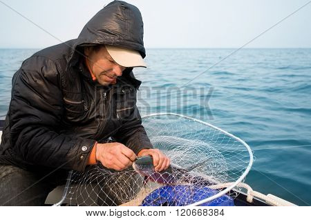 Early morning fisherman caught a big salmon in the sea. Coast Sea of Japan