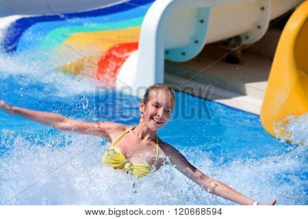 Happt teen girl on water slide at aquapark. Summer holiday.