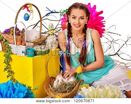 Woman with pigtails in easter style caress white rabbit  in basket.