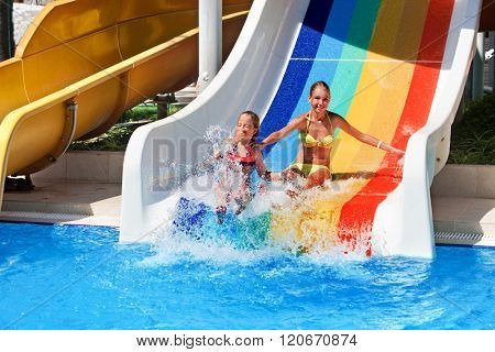 Two children on water slide at aquapark and thumb up. Summer holiday.