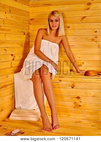 Young woman relaxing and posing in sauna. Healthy lifestyle.