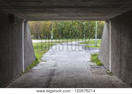 A look through a concrete tunnel.