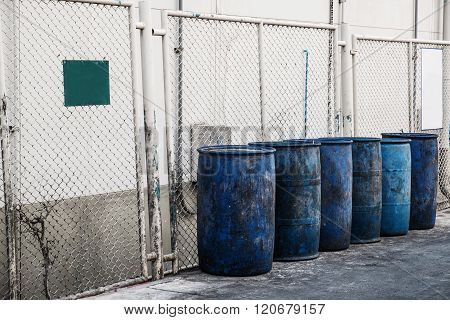 Dirty blue plastic garbage containers, with dirty blank signboard