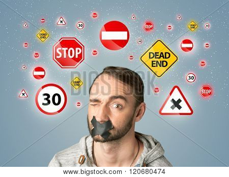 Young man with taped mouth and traffic signals around his head