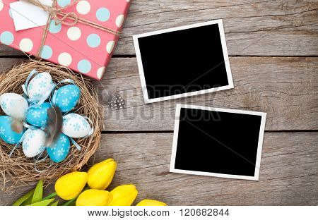 Easter background with blank photo frames, blue and white eggs, yellow tulips and gift box. Top view