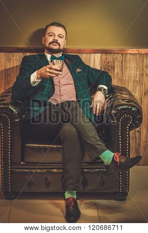 Confident old-fashioned man sitting in comfortable leather chair with glass of whisky in wooden interior at barber shop.