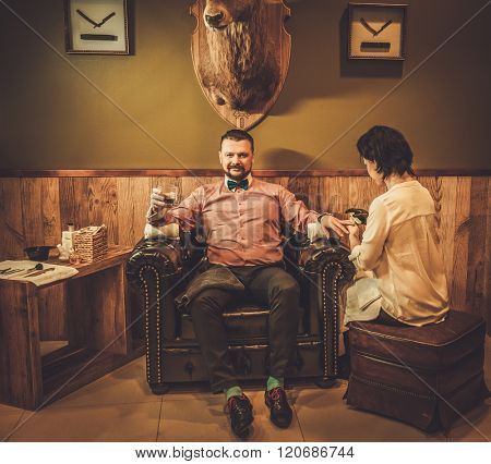 Confident old-fashioned man with glass of whisky doing male manicure in a barber shop.