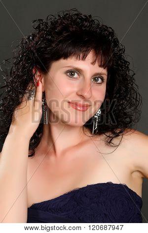 beautiful brunette in a black dress on a dark background