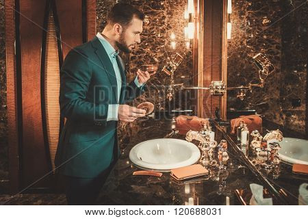 Confident well-dressed man in luxury bathroom interior.