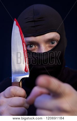 Man criminal in black mask with knife over dark blue background
