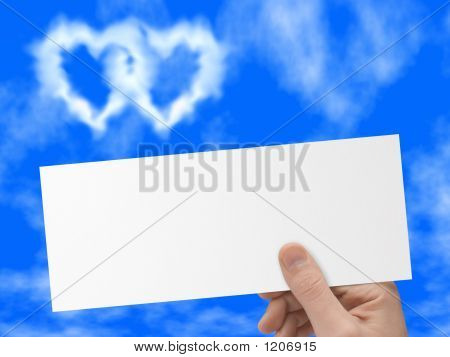 Postcard In Hand, Blue Sky And Heart-Shaped Clouds