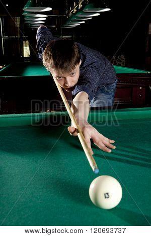 Young man playing billiards in the dark billiard club