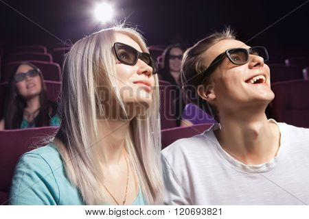 Young couple sitting at the cinema, watching a film. Cinema photo series