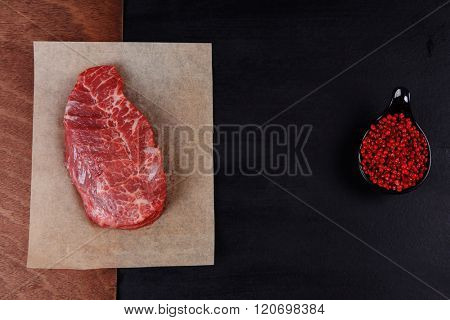 fresh raw beef rib eye steak on black walnut wooden table with red hot pepper spice in saucer
