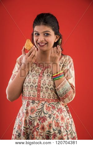 pretty indian young girl eating tasty samosa with green fried chilli, beautiful asian girl with samo