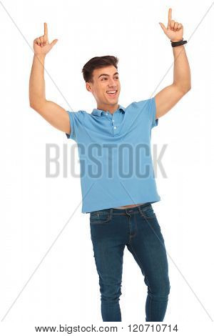 young man in blue shirt celebrating with both hands raised, pointing up while looking away in isolated studio background