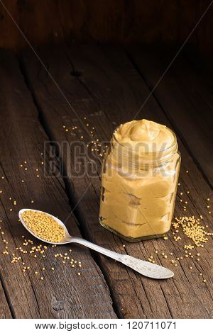 Fresh mustard sauce in a jar and mustard seeds scattered on a dark background.