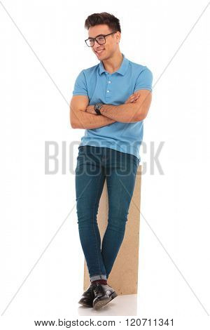 attractive man wearing glasses posing leaning on wooden box with hands and legs crossed while looking away from the camera in isolated studio background