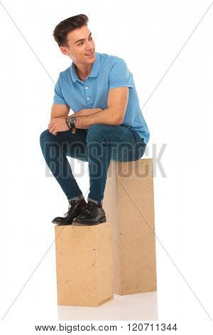 attractive hipster seated on boxes in isolated studio background while looking away from the camera