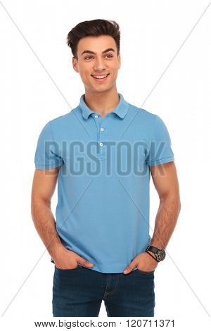 portrait of man in blue shirt posing in isolated studio background with hands in pockets while looking away from the camera