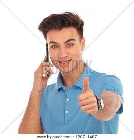 close portrait of attractive young man talking on the phone while showing thumbs up sign and looking at the camera in isolated studio background