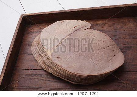 Image of sliced roast beef on wooden platter