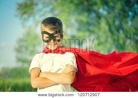 Super Hero Kid having fun outdoor. Superhero little boy over nature green blurred background. Little boy wearing superhero costume and having fun outdoors