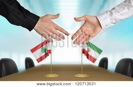 Lebanon and Iran diplomats shaking hands to agree deal