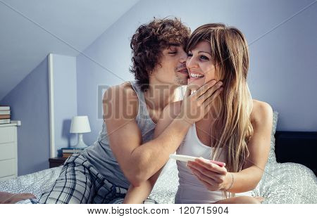 Young couple with pregnancy test in bedroom