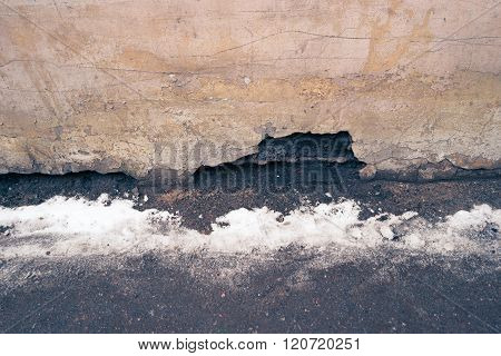 Weathered background, empty grunge urban street with snow and obsolete wall.