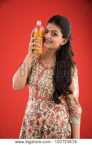 indian pretty girl with orange or mango juice bottle, isolated on red