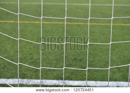 Close Up Detail Of A Soccer Net Against Green Grass On A Cloudy Day. Selective Focus
