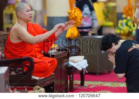SANGKHLABURI, THAILAND, JANUARY 24, 2016 :  A skilled Buddhist monk is blessing a woman  by throwing a rosary necklace around his neck in the Wat Wang Wiwekaram temple, Sanghklaburi, Thailand