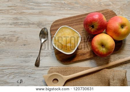 Organic applesauce with fresh apples on a wooden plate