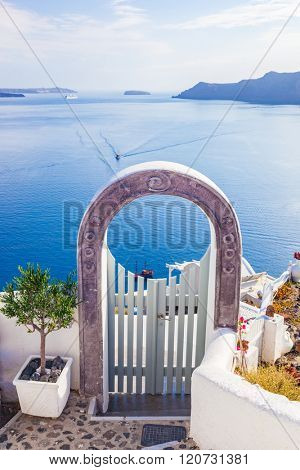 Traditional fence gate in Oia on Santorini island, Greece. Aegean sea and Caldera in the background. Blue sky, travel, vacation time.