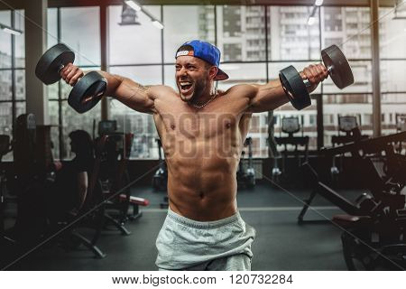 Handsome man lifting dumbbells at gym.