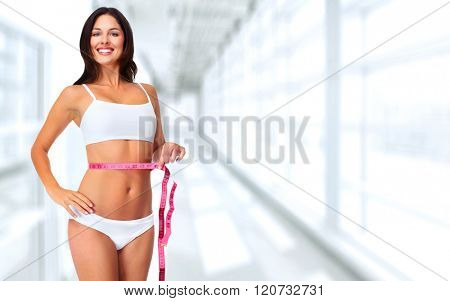 Woman with measuring tape over blue background.