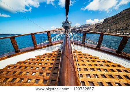 On board view from a traditional ship cruising on Aegean sea next to Santorini island. Wooden deck, sunny summer day.