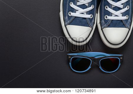 Hipster gumshoes and sun glasses arranged on black background from top view with space for text