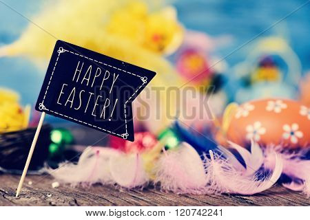 closeup of a black flag-shaped signboard with the text happy easter on a wooden surface full of feathers of different colors and some decorated eggs