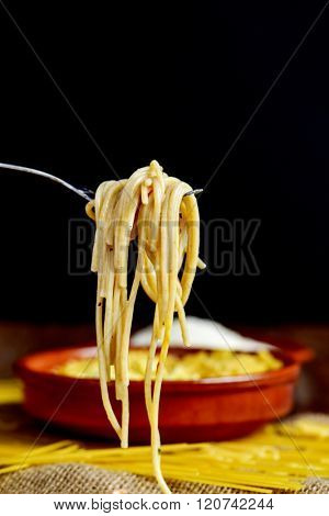 closeup of a some spaghetti alla carbonara in a fork, and an earthenware plate and some uncooked spaghetti on a table in the background
