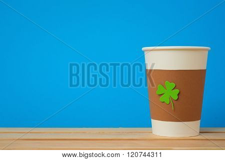 take away cup with cut and pasted green shamrock symbol on blue background