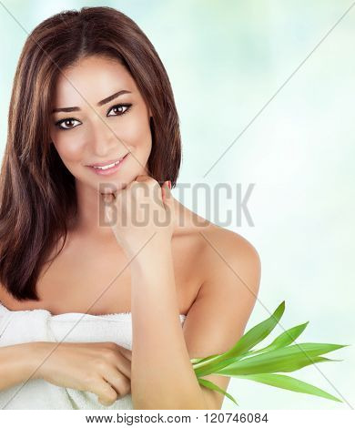 Portrait of gentle female holding fresh green leaves over blur and white background, with pleasure spending day in luxury spa salon